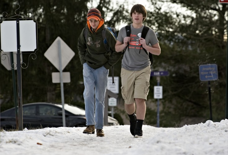 Cody Miller, 14, left, and Daniel McMullan, 15, right, walk across the snow- and ice-covered walkway on South Holliday Street in Strasburg on Thursday as temperatures hovered around the 20-degree mark. Shenandoah and Warren county schools were on a two-hour delay Thursday due to the cold weather.  Rich Cooley/Daily